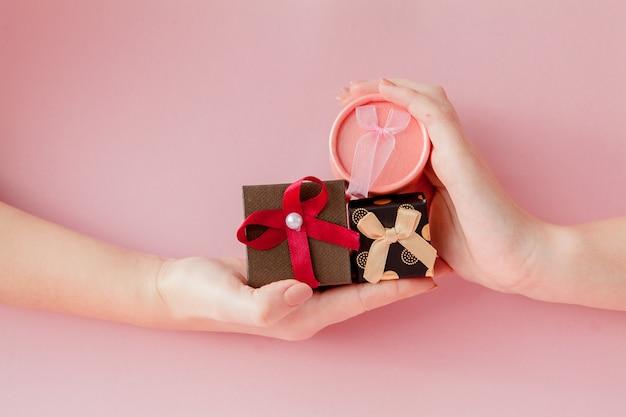 Kleine geschenkboxen in den frauenhänden auf einem rosa hintergrund. festliches konzept für valentinstag, muttertag oder geburtstag Premium Fotos