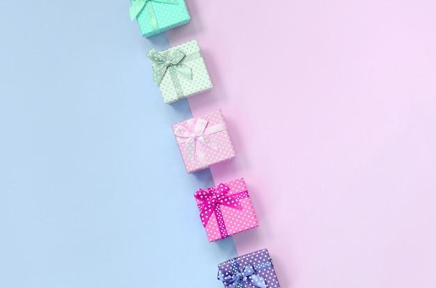 Kleine geschenkboxen in verschiedenen farben mit bändern liegen auf einem violetten und rosa Premium Fotos