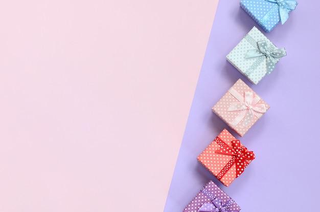 Kleine geschenkboxen in verschiedenen farben mit bändern liegen auf einem violetten und rosafarbenen farbhintergrund Premium Fotos