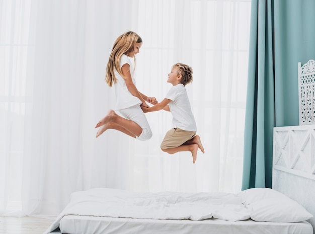 Kleine geschwister, die zusammen in bett springen Kostenlose Fotos