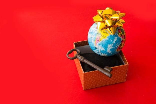 Kleine globale karte mit bogen nahe präsentkarton und schlüssel Kostenlose Fotos