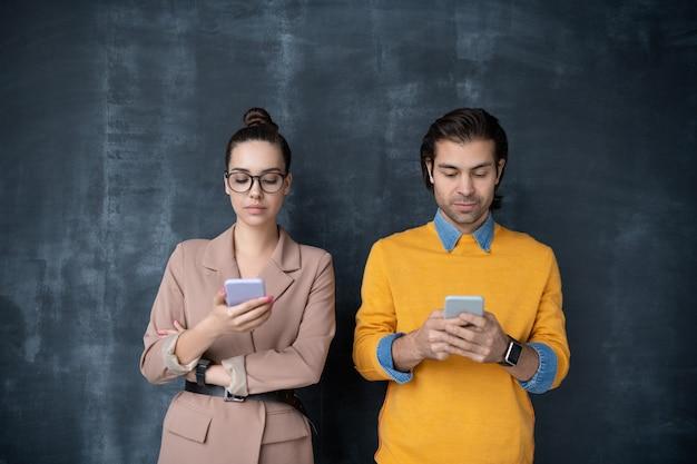 Kleine gruppe junger ernsthafter kollegen in schicker freizeitkleidung, die an der tafel stehen und in ihren mobilen geräten scrollen Premium Fotos