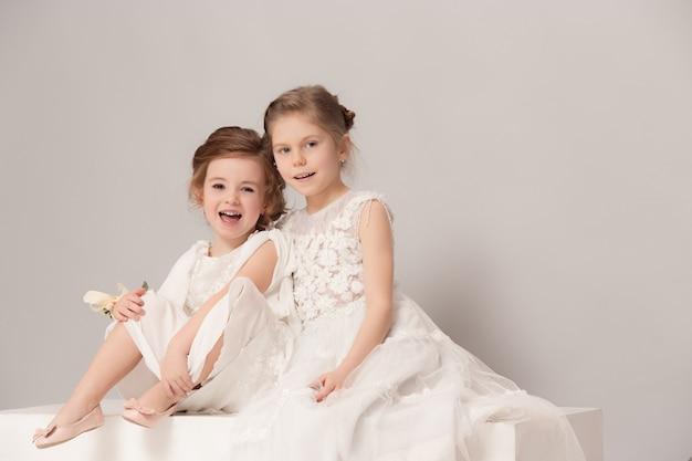 Kleine hübsche mädchen mit blumen in brautkleidern gekleidet. Kostenlose Fotos