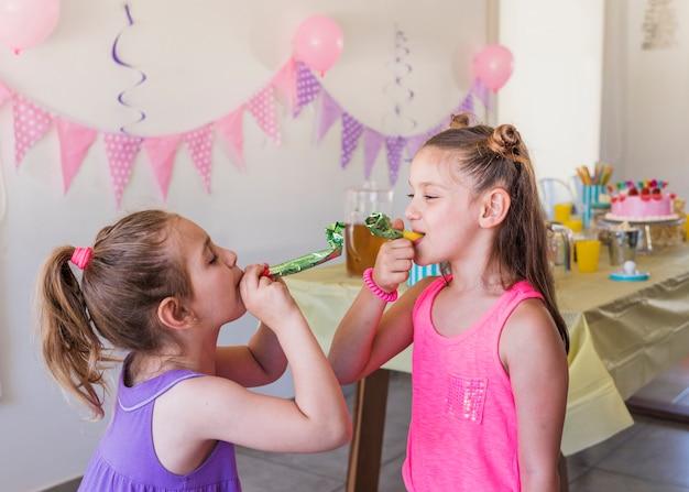 Kleine hübsche mädchen, welche das partyhorn genießt in der party durchbrennen Kostenlose Fotos
