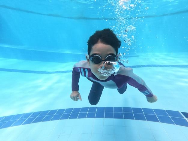 Kleine jungen, die am pool unter wasserschuß schwimmen und tauchen Premium Fotos