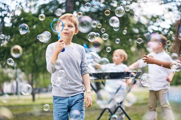 Kleine jungen, die seifenblasen machen Premium Fotos