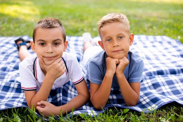 Kleine jungen posieren auf einer picknickdecke Kostenlose Fotos