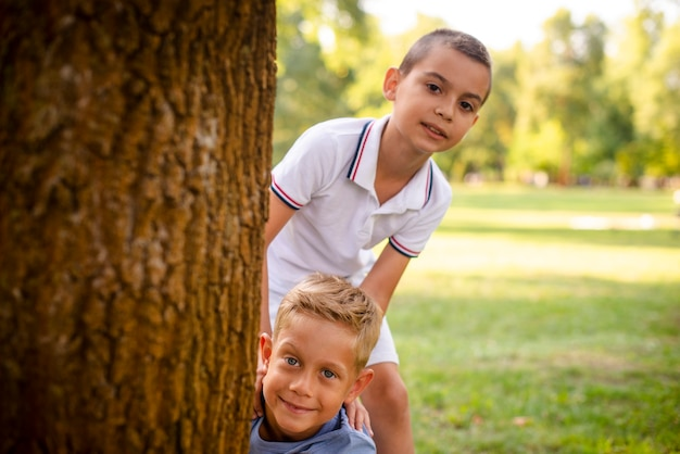 Kleine jungs posieren hinter einem baum Kostenlose Fotos