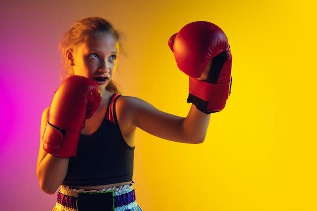 Kleine kaukasische weibliche kickboxertraining auf gradientenhintergrund im neonlicht, aktiv und ausdrucksstark Kostenlose Fotos