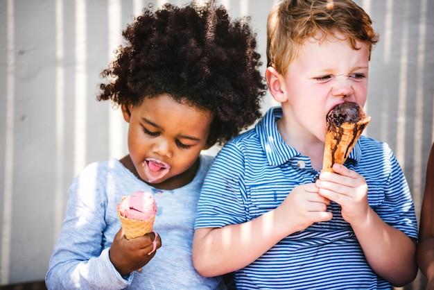 Kleine kinder, die leckere eiscreme essen Premium Fotos