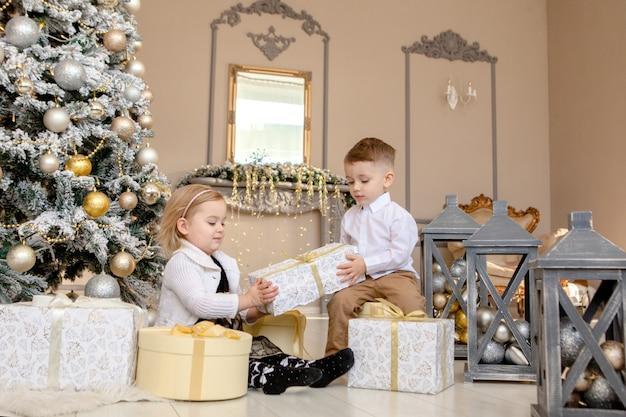 Kleine kinder freundschaft und liebe. kleiner junge, der einem kleinen mädchen ein geschenk für weihnachten gibt Premium Fotos