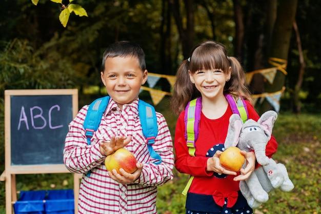 Kleine kinder gehen mit rucksäcken zur schule. zurück zur schule. bildung, schule, kindheit Premium Fotos