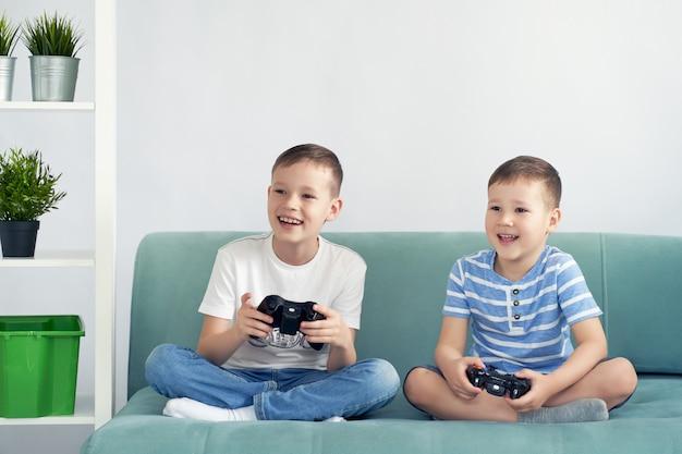 Kleine kinder spielen videospiele auf einem blauen sofa. Premium Fotos