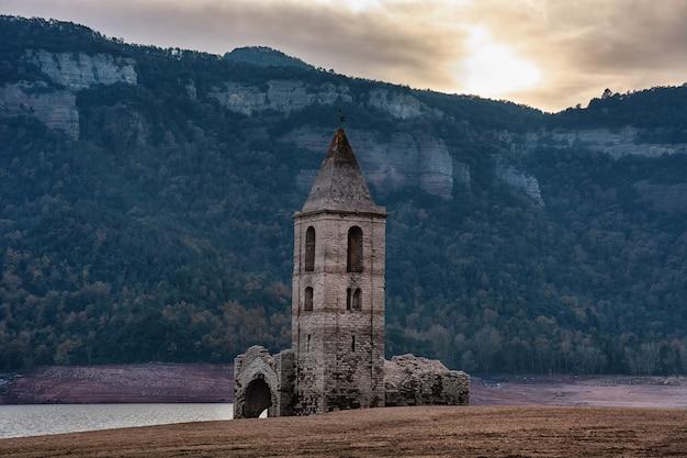 Kleine kirche in ruinen mit seinem glockenturm vor bergen u. neben einem fluss bei katalonien, spanien Premium Fotos