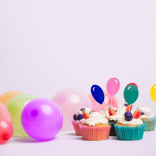 Kleine kleine kuchen mit luftballonen auf weißer tabelle Kostenlose Fotos