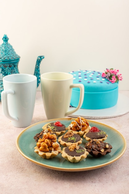 Kleine kuchen der vorderansicht mit schokolade und walnüssen zusammen mit blauer geburtstagstorte auf dem rosa schreibtisch Kostenlose Fotos