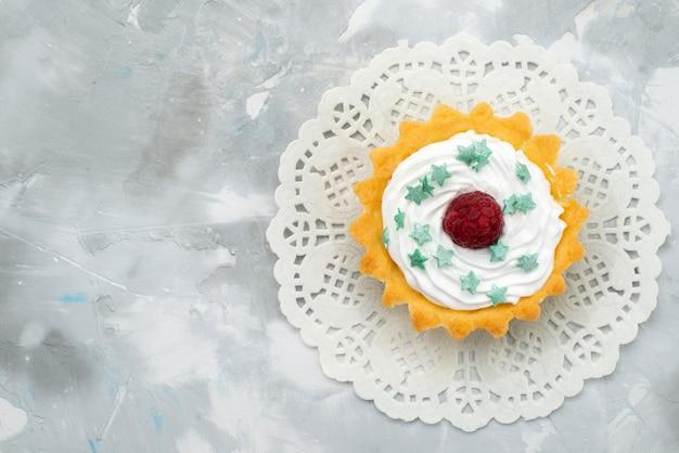 Kleine leckere torte mit sahne und himbeere von oben auf dem grauen schreibtisch süße sahne Kostenlose Fotos
