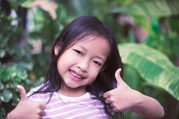 Kleine mädchen des asiatischen lächelns des porträts mit sehr gutem zeichen. Premium Fotos