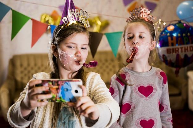 Kleine mädchen, die selfie auf party nehmen Kostenlose Fotos