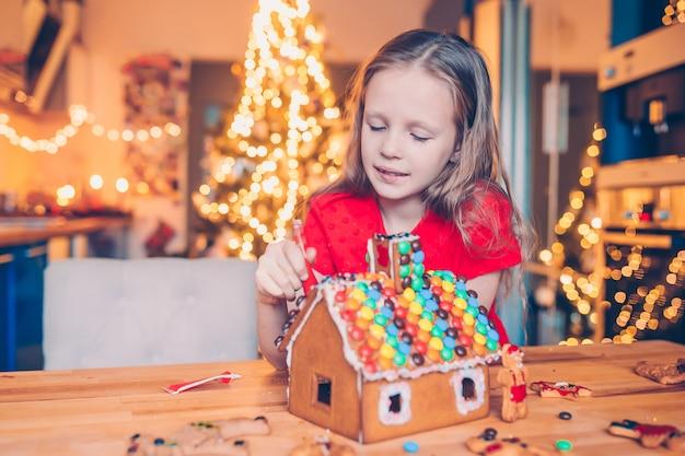Kleine mädchen, die weihnachtslebkuchenhaus am kamin in verziertem wohnzimmer machen. Premium Fotos
