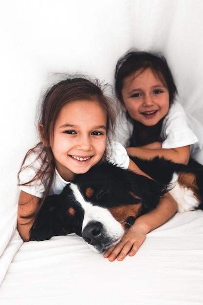 Kleine mädchen im bett mit hund berner sennenhund, freundschaft Premium Fotos