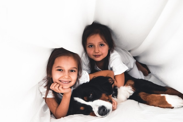 Kleine mädchen im bett mit hund berner sennenhund Premium Fotos