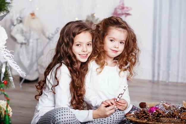 Kleine mädchen in bequemer hauskleidung, die auf boden in schönen weihnachtsdekorationen sitzt Premium Fotos