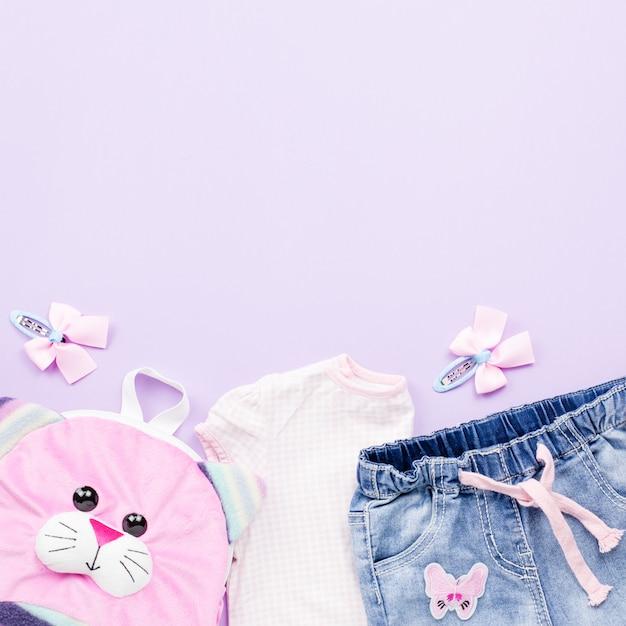 Kleine mädchen kleider sammlung flach lag mit t-shirt, jeans, rucksack auf pastell Premium Fotos