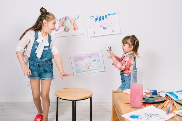 Kleine mädchen laufen mit gemalten fingern Kostenlose Fotos