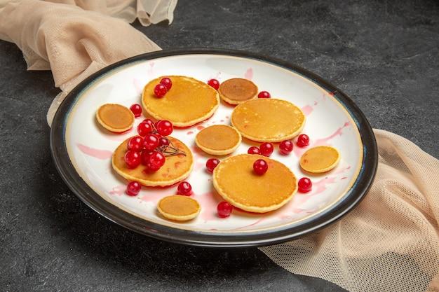 Kleine pfannkuchen mit roten beeren auf dunkelgrau Kostenlose Fotos