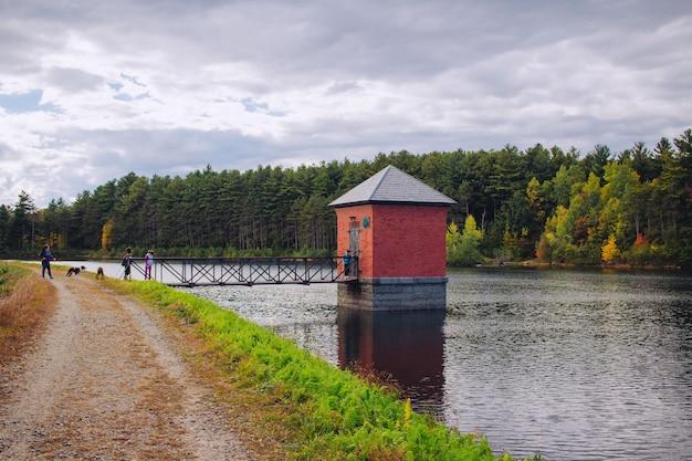 Kleine rote hütte an einem fluss gebaut und mit einer brücke mit atemberaubender natur verbunden Kostenlose Fotos