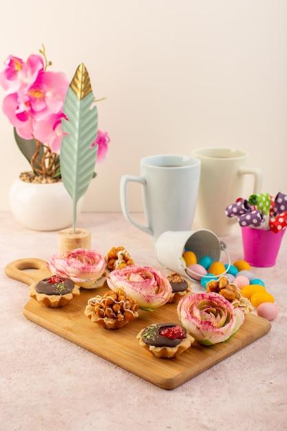 Kleine schokoladenkuchen von vorne mit blumen und pflanzen auf dem rosa schreibtisch Kostenlose Fotos