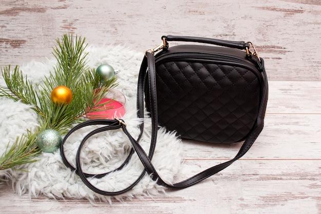 Kleine schwarze weibliche handtasche, tannenzweig mit verzierungen, kerze. mode-konzept Premium Fotos