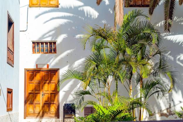 Kleine spanische terrasse mit palmen und banch. alte holztür und fenster in garachico, teneriffa, spanien Kostenlose Fotos
