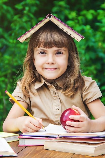 Kleine studentin mit einem roten apfel. selektiver fokus natur. Premium Fotos