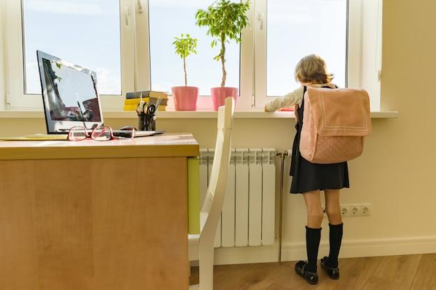 Kleine studentin mit rucksack in der schuluniform schaut aus dem fenster heraus Premium Fotos