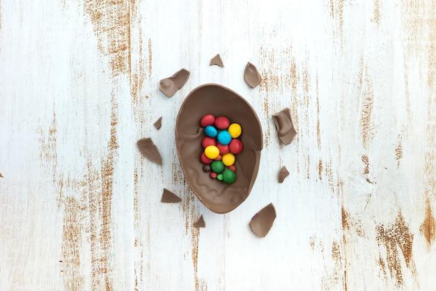 Kleine süßigkeiten im offenen schokoladenei auf tabelle Kostenlose Fotos