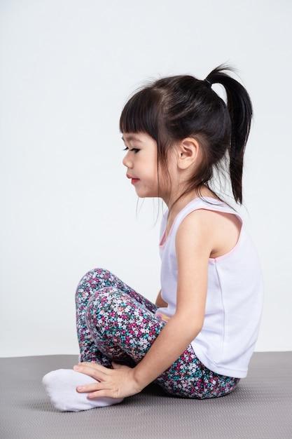 Kleine tochter, die auf yogaauflage für übung sitzt Kostenlose Fotos