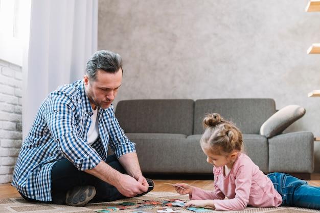 Kleine tochter und vater, die zu hause puzzlen spielt Kostenlose Fotos