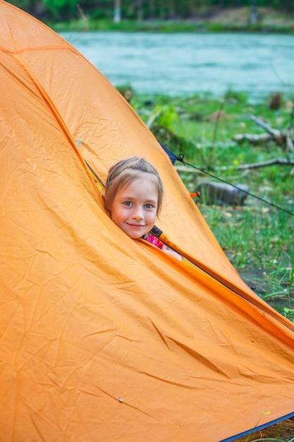 Kleine touristin schaut aus dem orangefarbenen zelt Premium Fotos