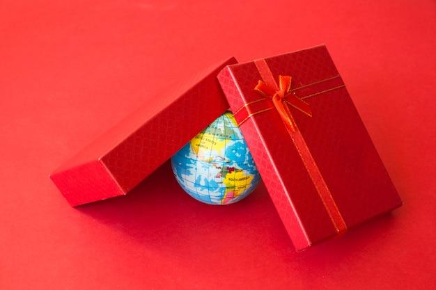 Kleine weltkarte unter der geschenkbox Kostenlose Fotos