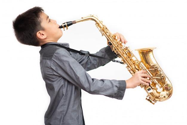 Kleiner asiatischer musikerjunge, der saxophon spielt Premium Fotos