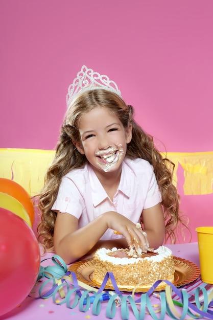 Kleiner blonder girleating kuchen der geburtstagsfeier mit den händen Premium Fotos