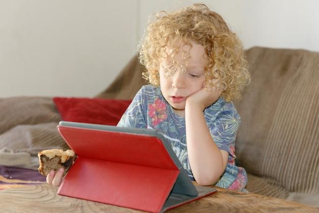 Kleiner blonder junge, der tablet-computer verwendet Premium Fotos