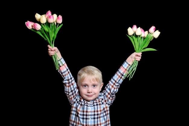 Kleiner blonder junge, der zwei blumensträuße von tulpen hält. porträt. Premium Fotos
