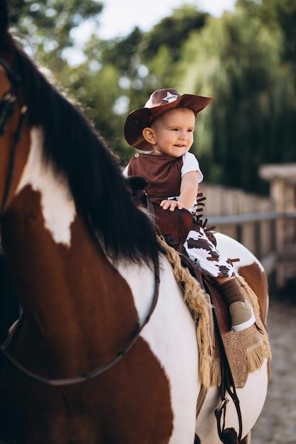 Kleiner cowboy, der auf einem pferd sitzt Kostenlose Fotos
