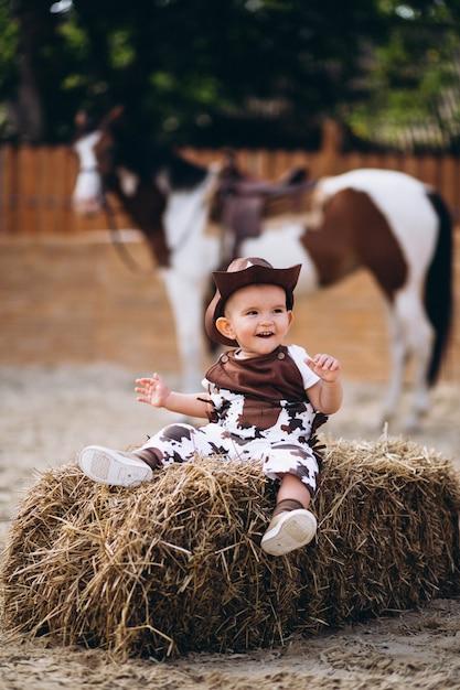 Kleiner cowboy, der auf heu sitzt Kostenlose Fotos