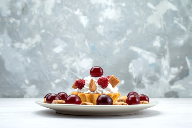 Kleiner cremiger kuchen mit himbeeren und kleinen keksen auf weißlichtschreibtisch, obstkuchen süße beerencremekirsche Kostenlose Fotos