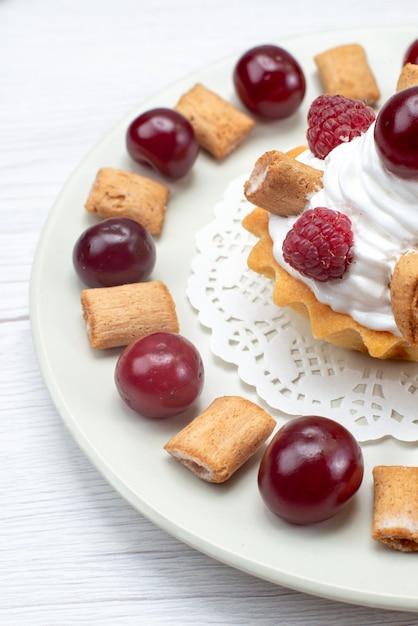 Kleiner cremiger kuchen mit himbeerkirschen und kleinen keksen auf weißlichter, süßer beerencreme mit obstkuchen Kostenlose Fotos
