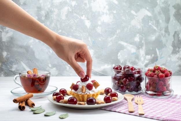 Kleiner cremiger kuchen mit himbeerkirschen und kleinen keksen tee zimt auf weißlicht schreibtisch, frucht süße beerencreme Kostenlose Fotos
